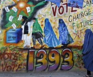 Afghan woman walks past a wall with election graffiti